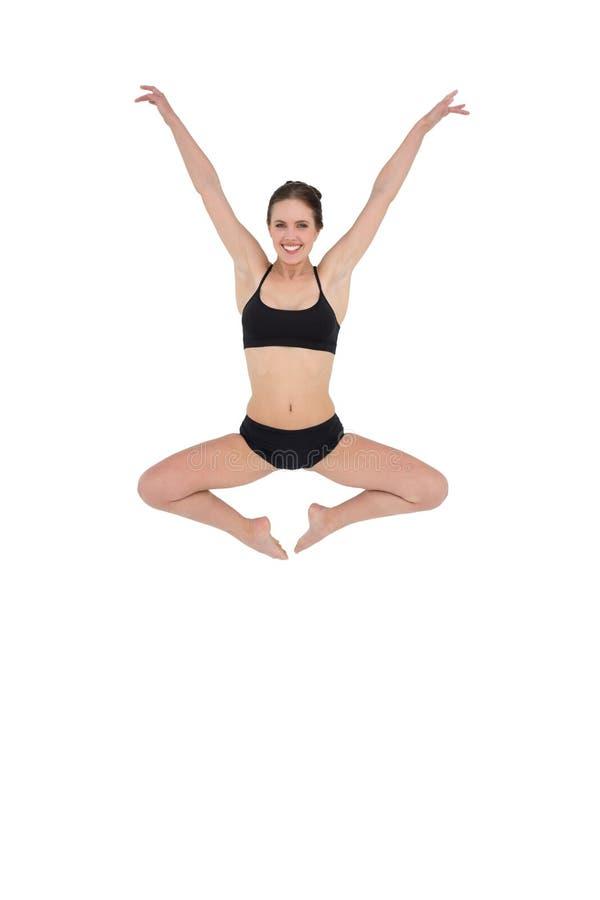 Sportig banhoppning för ung kvinna som isoleras på vit bakgrund royaltyfri bild