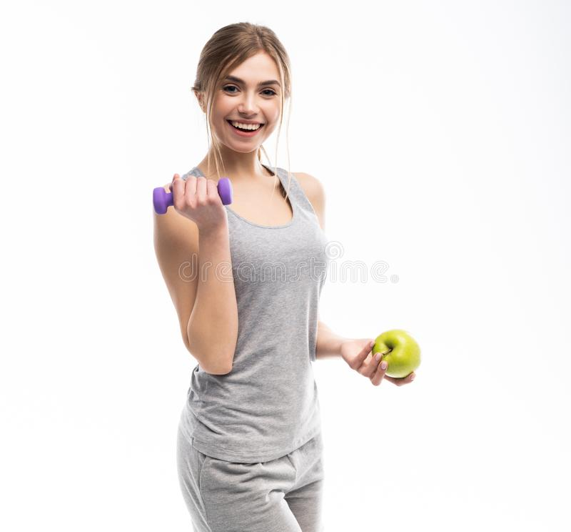 Sportig färdig kvinna som rymmer hantelvikter i en och äpplefrukt i en annan hand Kondition och sunt banta begrepp royaltyfri bild