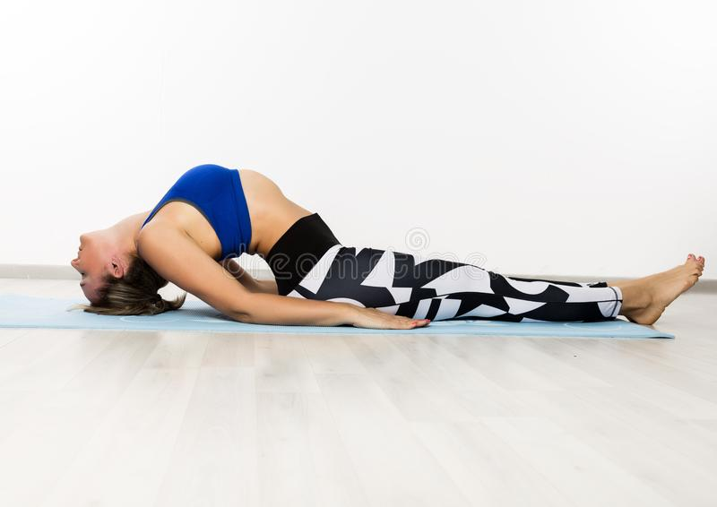 Sportig för övningsyoga för ung kvinna asana i grupp Begreppet av lugn och kopplar av royaltyfri foto