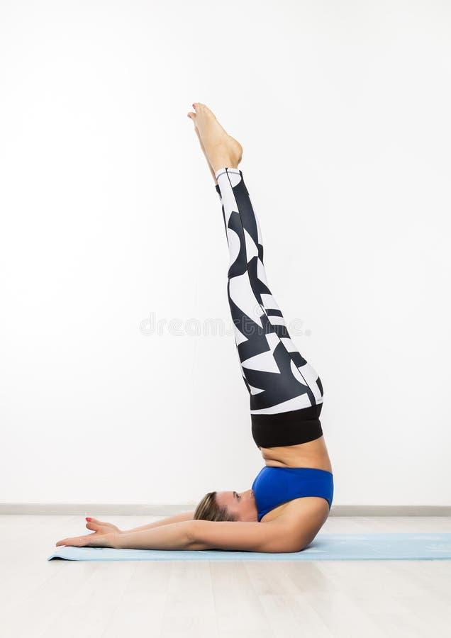 Sportig för övningsyoga för ung kvinna asana i grupp Begreppet av lugn och kopplar av fotografering för bildbyråer