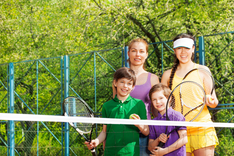 Sportig familj som förbereder sig att starta en tennisuppsättning royaltyfri fotografi