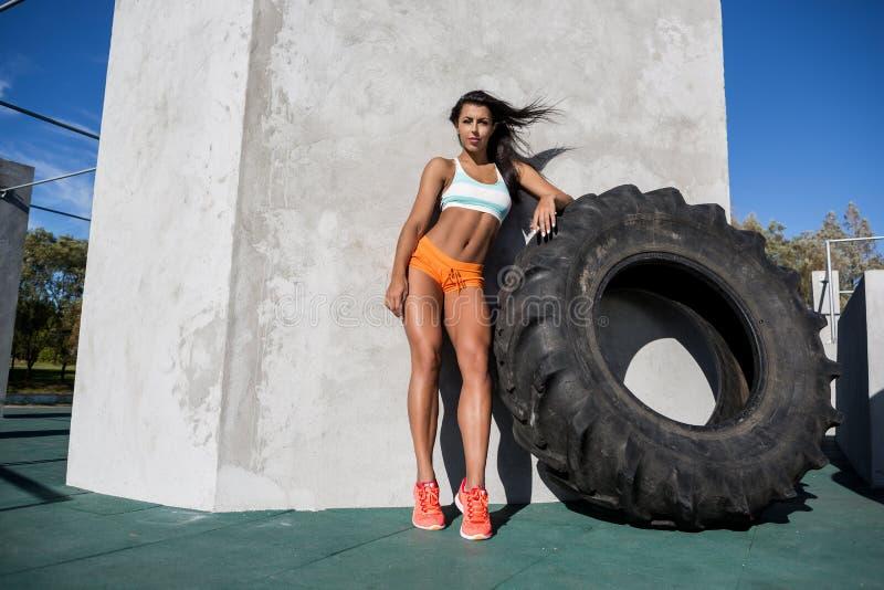 Sportig flickaövning med det stora gummihjulet arkivbilder