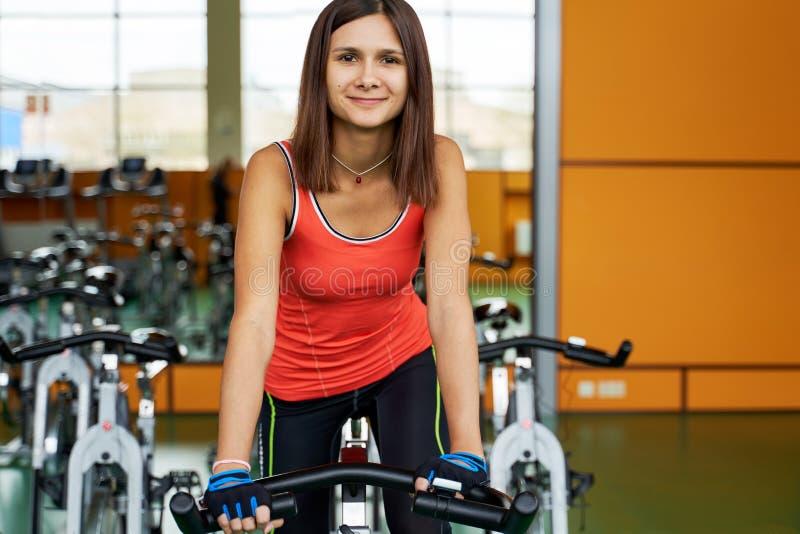 Sportig flicka i t-skjorta, damasker och handskar som trampar p? den station?ra cykeln H?rlig kvinnaridningcykel i idrottshallen royaltyfri foto