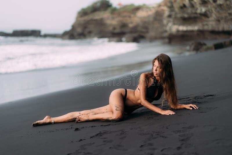 Sportig flicka med den sexiga kroppen i svart swimwear som vilar på den svarta sandstranden arkivfoton