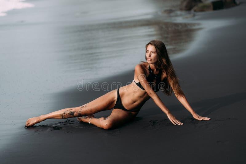 Sportig flicka med den sexiga kroppen i svart swimwear som vilar på den svarta sandstranden arkivbilder