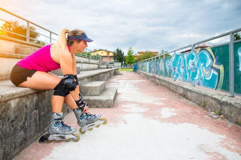 Sportig flicka som du ändrar för att göra rollerblade på momenten av fet royaltyfria foton