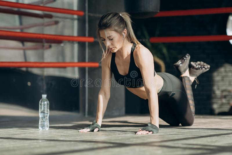 Sportig flicka utförande skjuta-UPS på golv attraktivt kvinnabarn arkivfoton