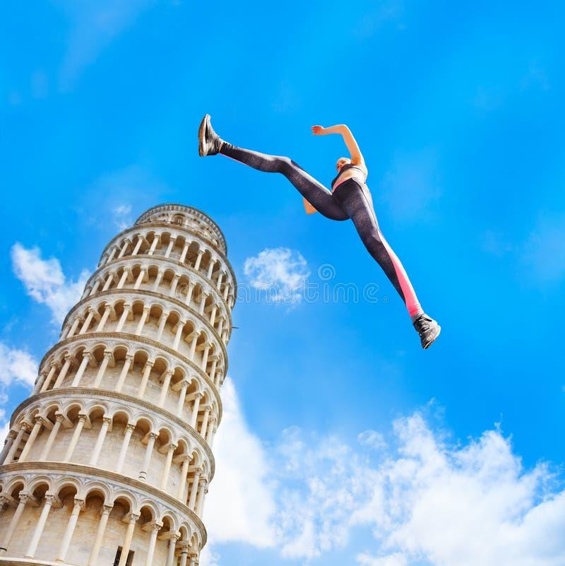 Sportig flickabanhoppning nära det Pisa tornet arkivfoto