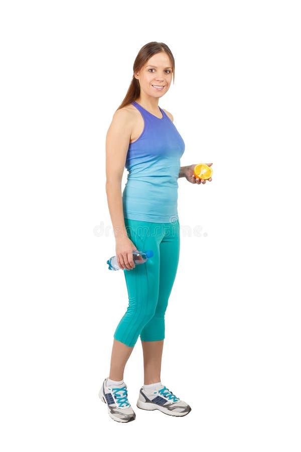 Sportig gravid kvinna med en flaska av vatten och apelsinen som isoleras arkivfoto