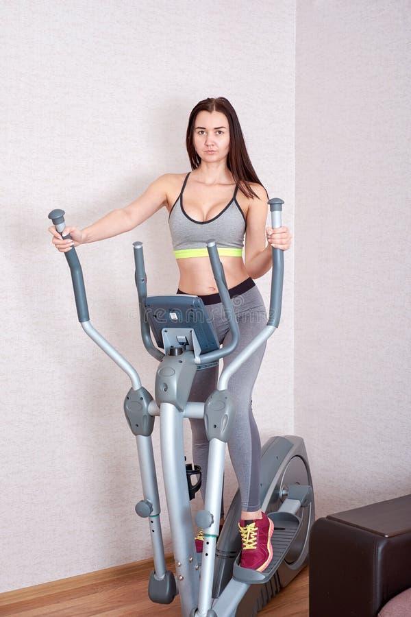 Sportig härlig kvinna som hemma övar för att bli färdigt arkivfoton