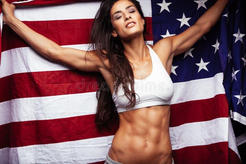 Sportig hållande amerikanska flaggan för ung kvinna royaltyfria foton