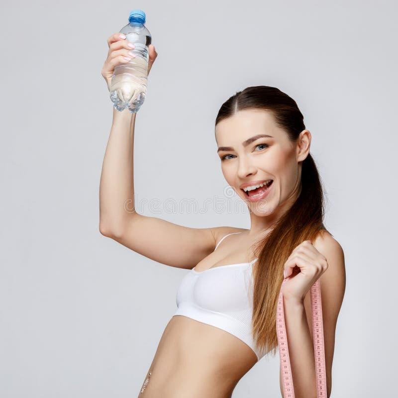 Sportig kvinna över grått bakgrundsdricksvatten arkivbild