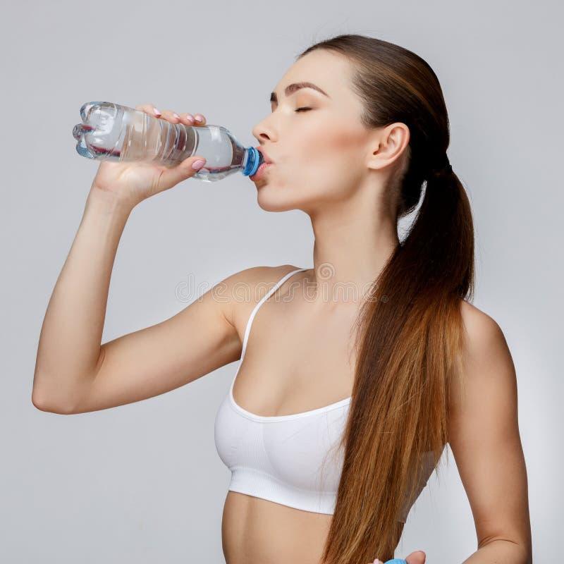 Sportig kvinna över grått bakgrundsdricksvatten royaltyfri foto