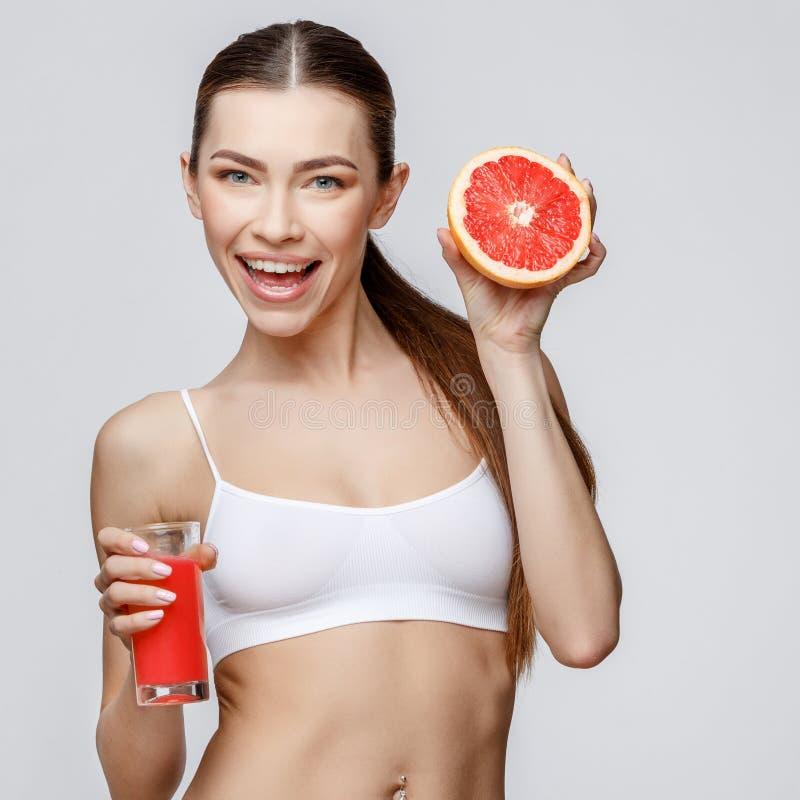 Sportig kvinna över hållande exponeringsglas för grå bakgrund av grapefruktfruktsaft royaltyfri fotografi