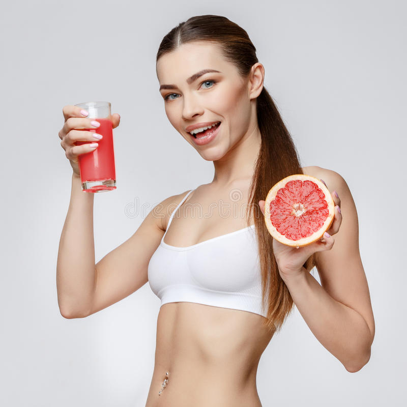 Sportig kvinna över hållande exponeringsglas för grå bakgrund av grapefruktfruktsaft royaltyfria foton