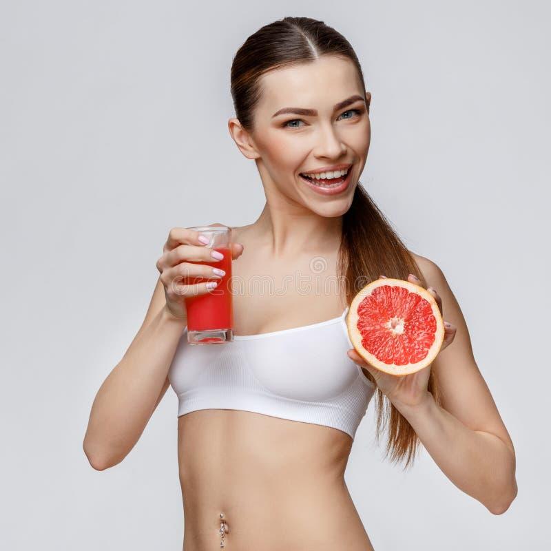 Sportig kvinna över hållande exponeringsglas för grå bakgrund av grapefruktfruktsaft arkivbild