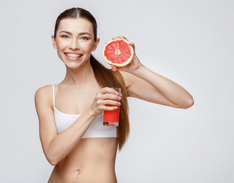 Sportig kvinna över hållande exponeringsglas för grå bakgrund av grapefruktfruktsaft arkivfoto