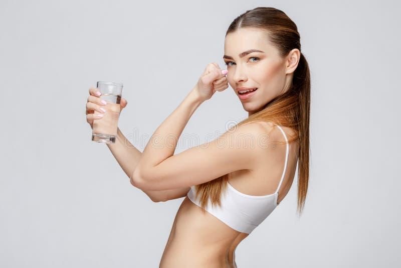 Sportig kvinna över hållande exponeringsglas för grå bakgrund av vatten arkivbilder