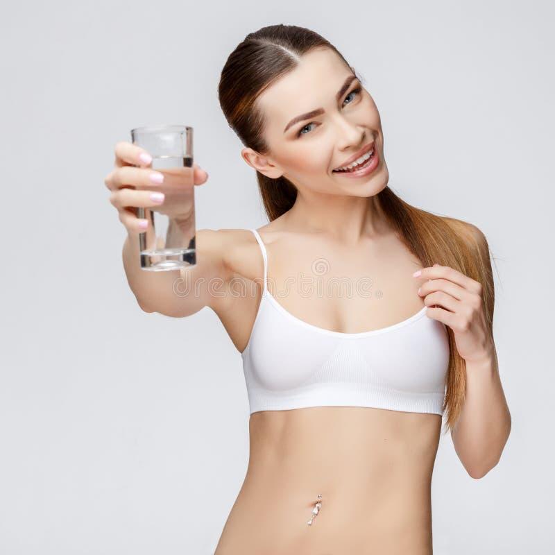 Sportig kvinna över hållande exponeringsglas för grå bakgrund av vatten royaltyfri fotografi