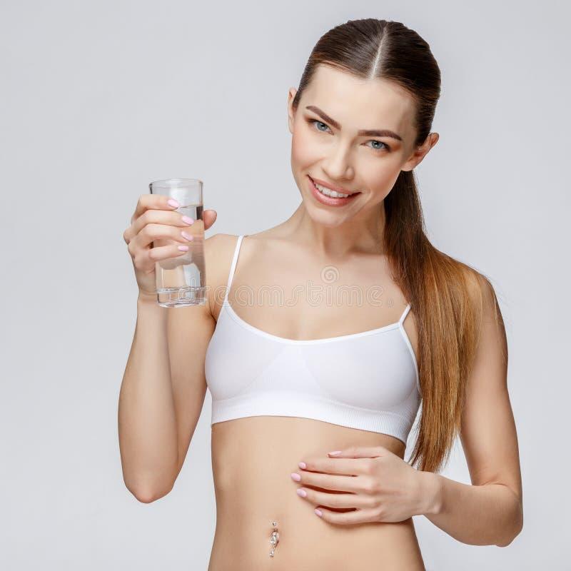Sportig kvinna över hållande exponeringsglas för grå bakgrund av vatten royaltyfri foto