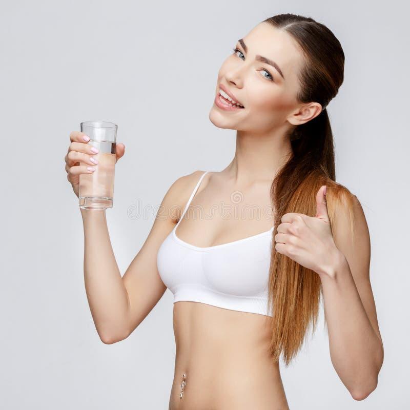 Sportig kvinna över hållande exponeringsglas för grå bakgrund av vatten arkivbild