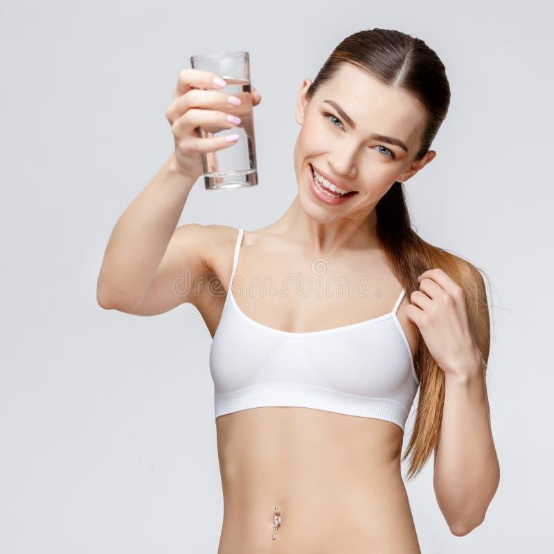 Sportig kvinna över hållande exponeringsglas för grå bakgrund av vatten arkivfoton