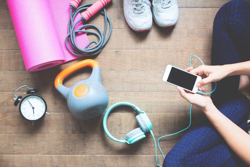 Sportig kvinna för bästa sikt som använder smartphonen med konditionutrustningnolla royaltyfria bilder