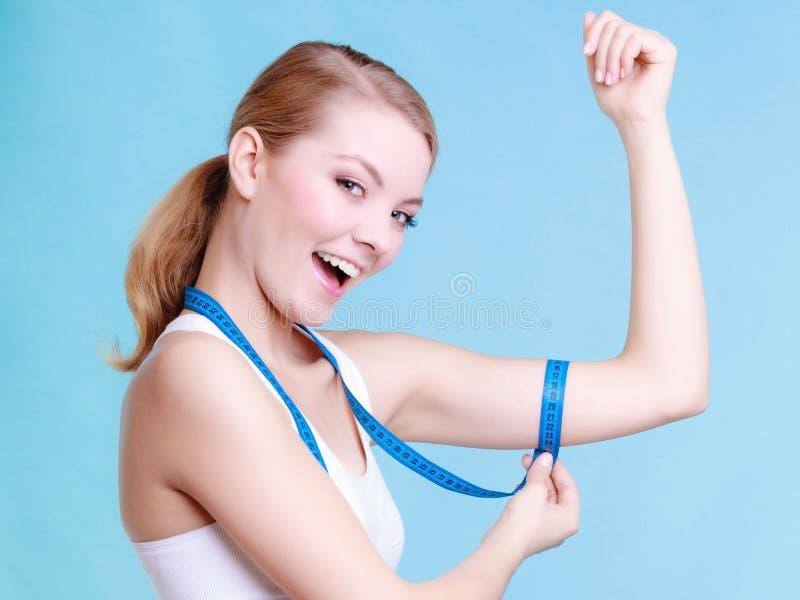 Sportig kvinna för konditionflicka som mäter hennes biseps på blått fotografering för bildbyråer