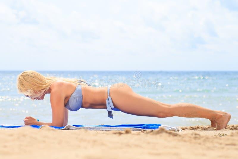 Sportig kvinna i plankaposition på stranden En sund livsstil royaltyfri foto