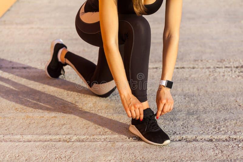 Sportig kvinna i svart sporwear på morgonen på gataanseende på knä och att förbereda sig för utbildning som binder skosnöre på gy royaltyfri foto