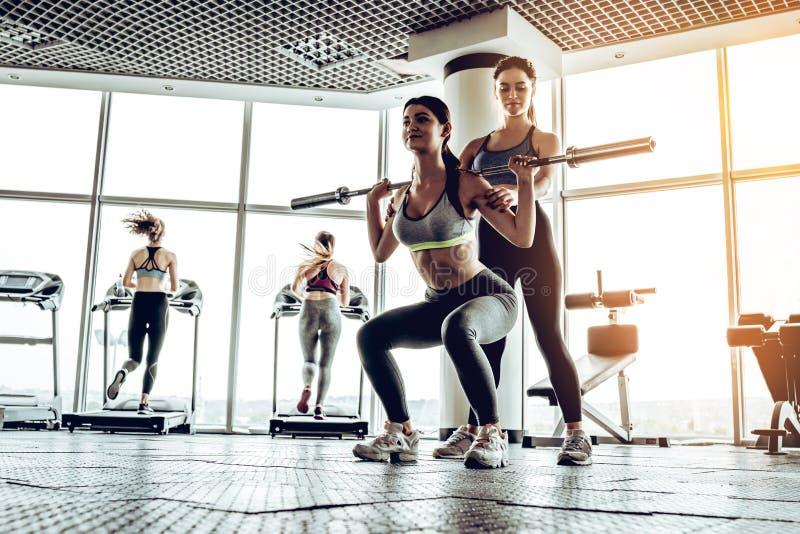 Sportig kvinna som övar med skivstången i idrottshall fotografering för bildbyråer