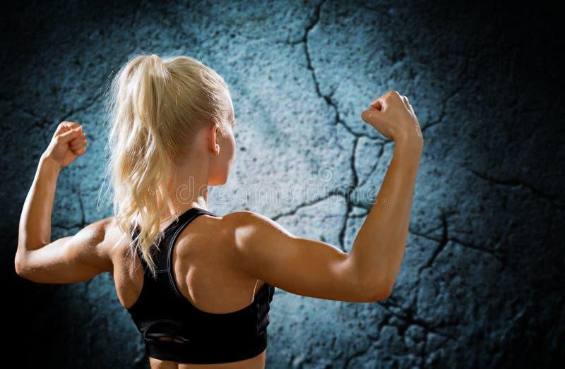 Sportig kvinna som böjer och visar biceps från baksida arkivfoton