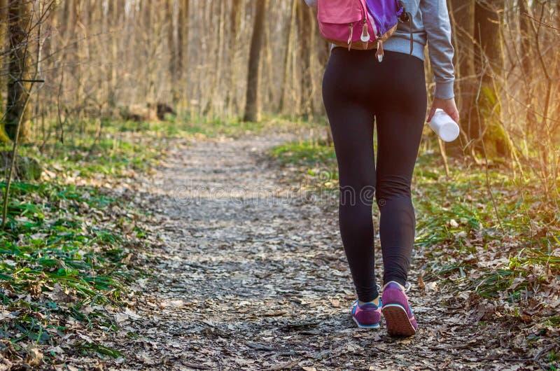 Sportig kvinna som går i skogen arkivbild