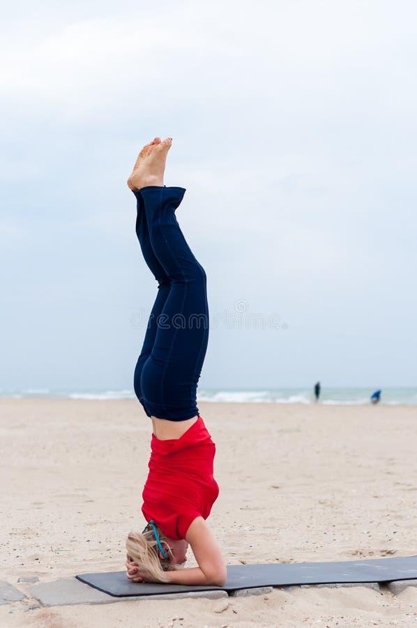 Sportig kvinna som gör den stöttade huvudståenden, yogaasana Sirsasana, Shirshasana, Sirshasana, huvudstående på havsbakgrund royaltyfri bild