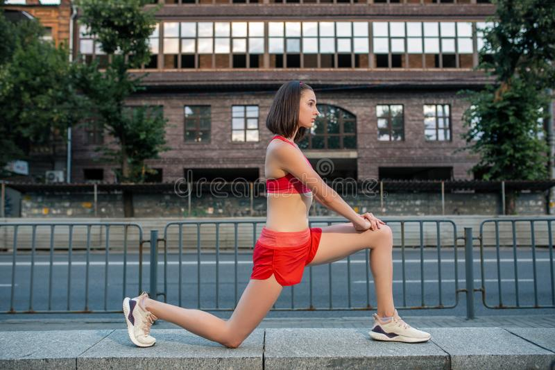 Sportig kvinna som sträcker och värmer ben upp, innan att köra stads- konditiongenomkörare Sport och sunt livsstilbegrepp royaltyfria bilder