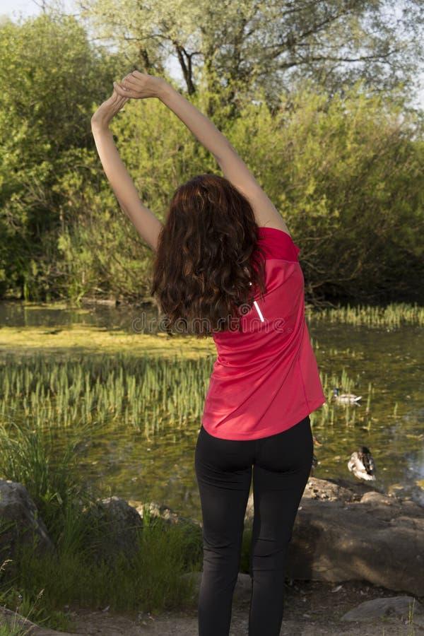 Sportig kvinna som tillbaka sträcker henne efter sportar i natur fotografering för bildbyråer
