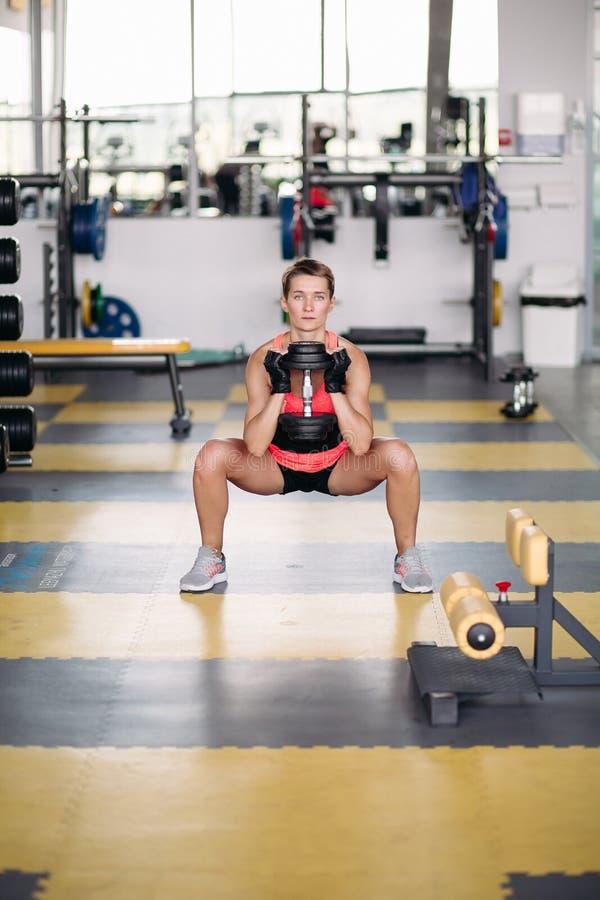 Sportig kvinnadanandeövning som squatting med hantlar i idrottshall arkivfoton