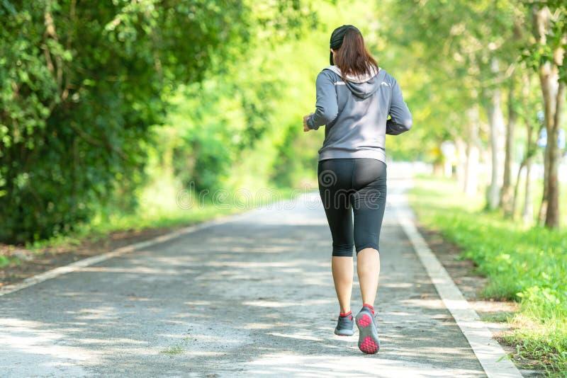 Sportig kvinnalöpare som kör till och med vägen Genomk?rare i en parkera Utomhus- genomk?rare i en parkera arkivbilder