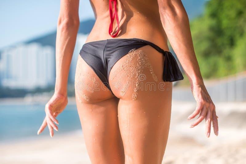 Sportig kvinnlig ände in med två sandhandtryck Den kantjusterade bilden av den unga kvinnan som står henne vände tillbaka, till a arkivbilder