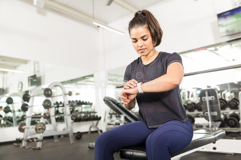 Sportig kvinnlig kontrollerande konditionaktivitet på den smarta klockan i idrottshall arkivfoto