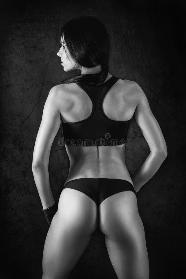 Sportig kvinnlig med den perfekta kroppen mot mörk bakgrund Konditionkvinna i sportswear med den ideala konditionkroppen monokrom arkivbilder