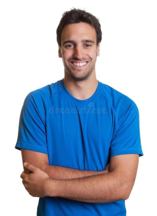 Sportig latinsk grabb med korsade armar i en blå skjorta royaltyfri foto