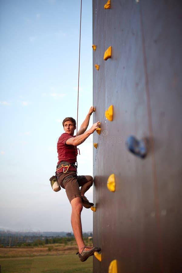 Sportig manövning vaggar klättring i idrottshall på konstgjort vaggar utbildningsväggen utomhus Barnet talanted klättraregrabben  royaltyfri foto