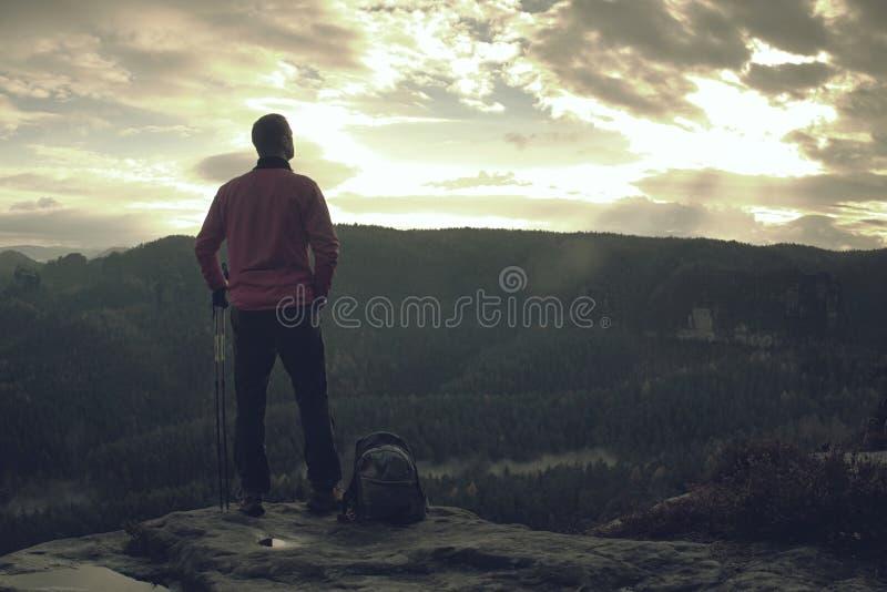 Sportig man på bergmaximumet som ser på bergdalen fotografering för bildbyråer