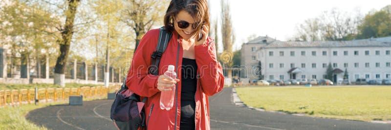 Sportig mogen kvinna för stående på stadion, panorama- baner, i sportkläder för utbildning, med flaskan av vatten som talar på royaltyfri bild