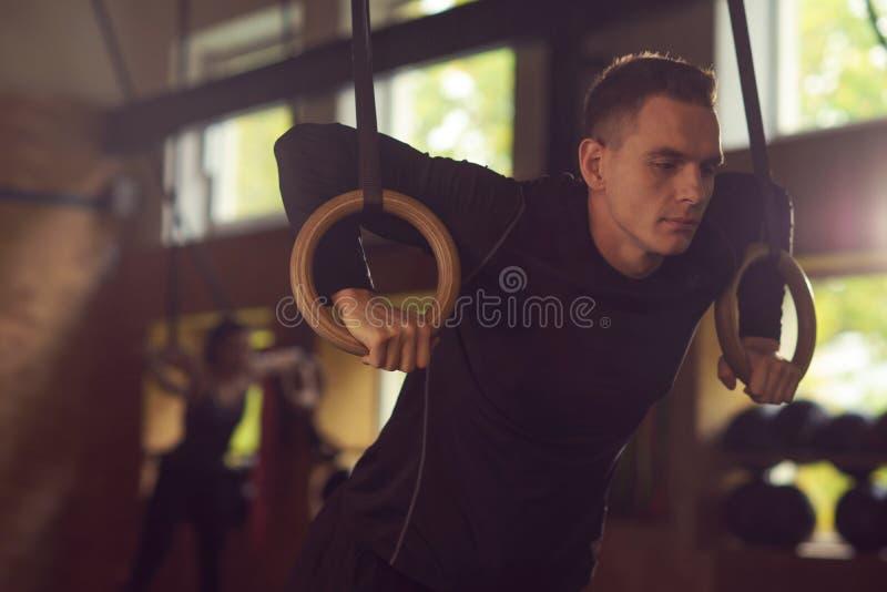 Sportig och idrotts- idrottsman för passform som, arbetar i en idrottshall Manutbildning genom att använda gymnastiska cirklar Sp arkivbild