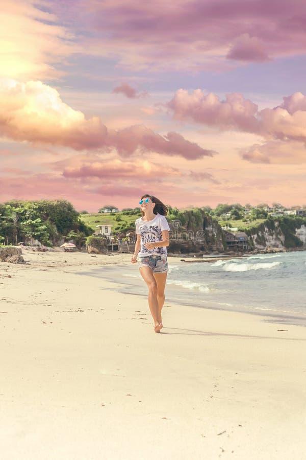 Sportig och sund ung kvinna i solglasögon som kör på den tropiska stranden under solnedgång man för bali town för solnedgång för  arkivbilder