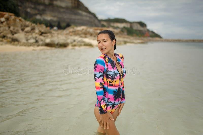 Sportig, sexig och härlig flicka för barn, i baddräkt som vilar på den exotiska stranden i sommar arkivbilder
