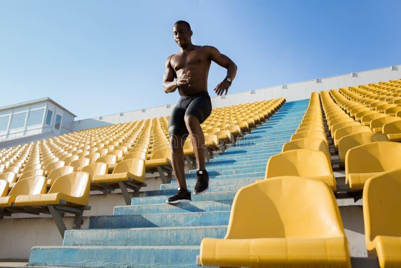 Sportig ung afrikansk manlöpare som uppför trappan kör arkivbild