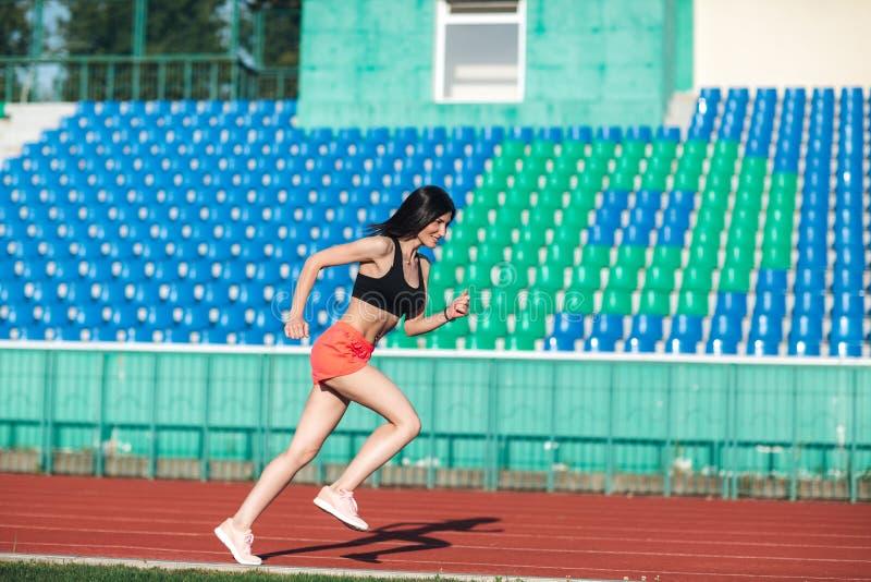 Sportig ung brunettkvinna i rosa kortslutningar och ärmlös tröja som kör på stadion Sund aktiv livsstil Sommarsportaktivitet royaltyfria bilder
